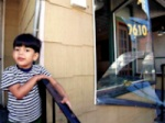 Enlarge: Young child next to damaged store.